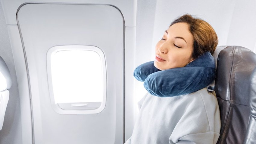 girl sleeping on the plane with a pillow