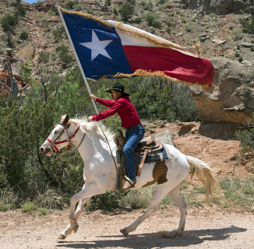 Photo of man on horseback holding a Texas state flag
