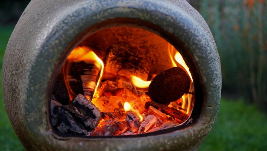 Close up of a Chiminea on fire in a garden.