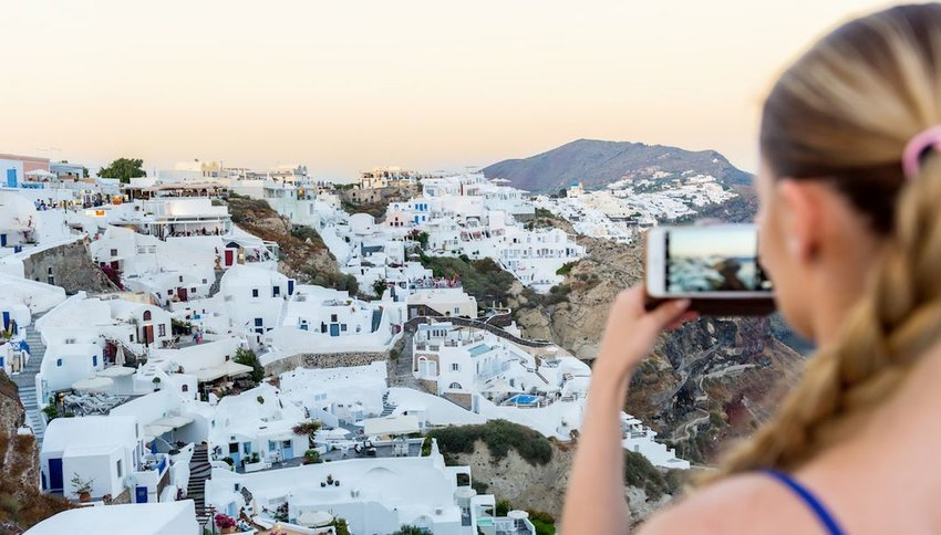 Female tourist capturing photo of Oia, Santorini