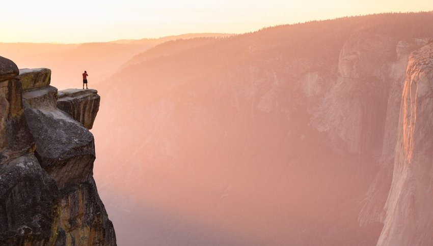 hiker stands at the edge of a cliff at Taft Point