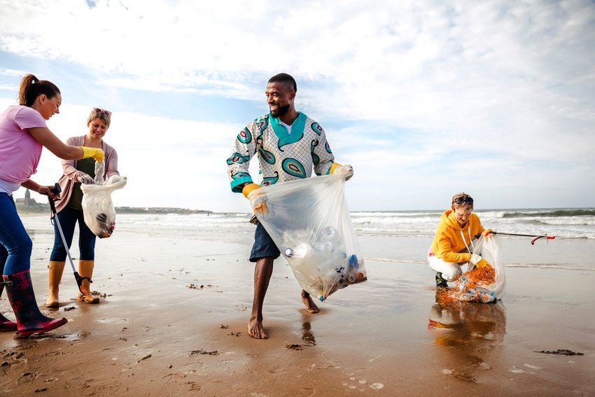 Group of people picking up trash on a beach