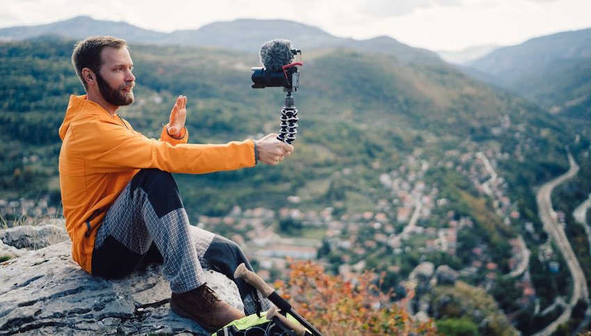 tourist hiking and vlogging on the mountain top