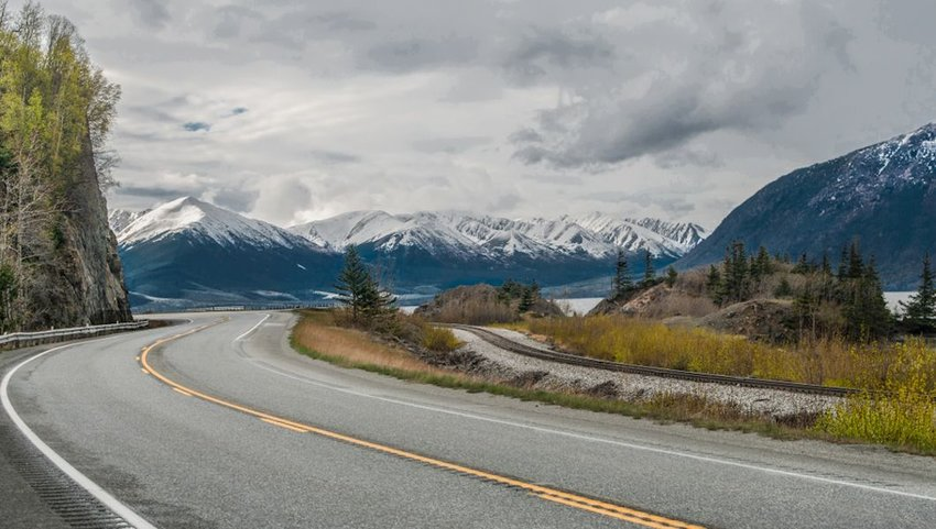 Seward Highway curving by snow-covered mountains outside Anchorage