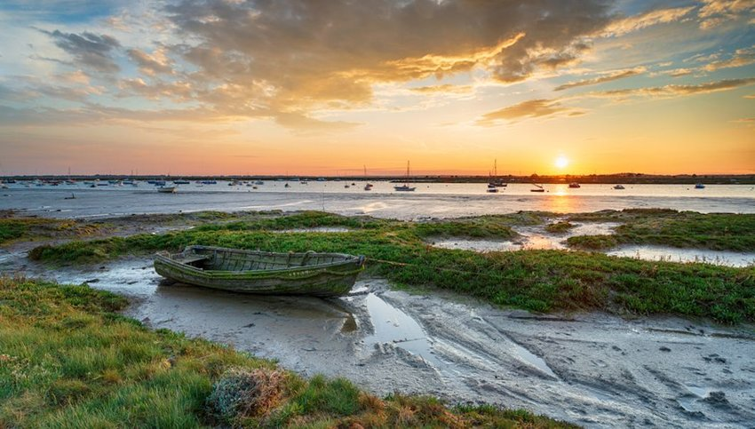 old boat in the salt marsh at West Mersea at sunset
