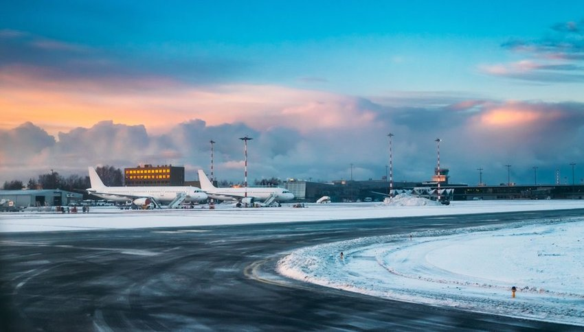 Aircraft stand on ground at International Airport terminal in snow