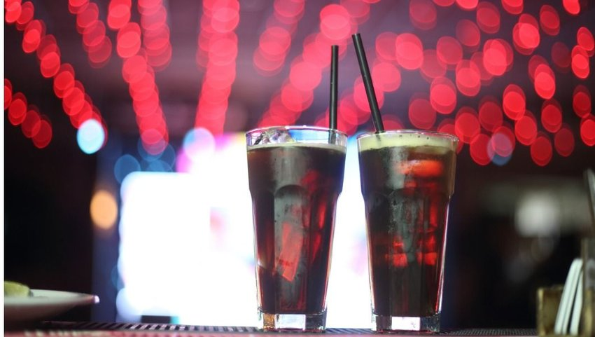 Front view of Fernet cocktails on a bar with red lights in background