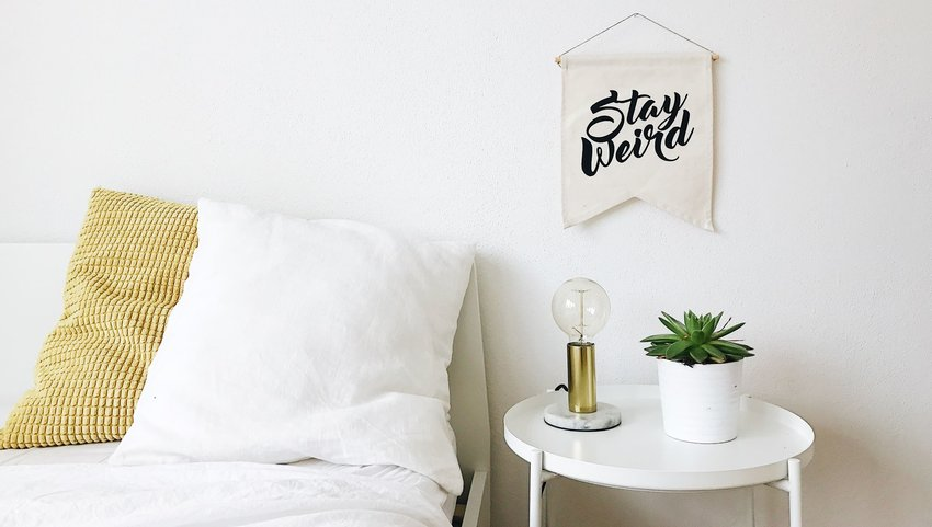 "White bed with pillows next to a nightstand and a sign that says ""Stay Weird"""