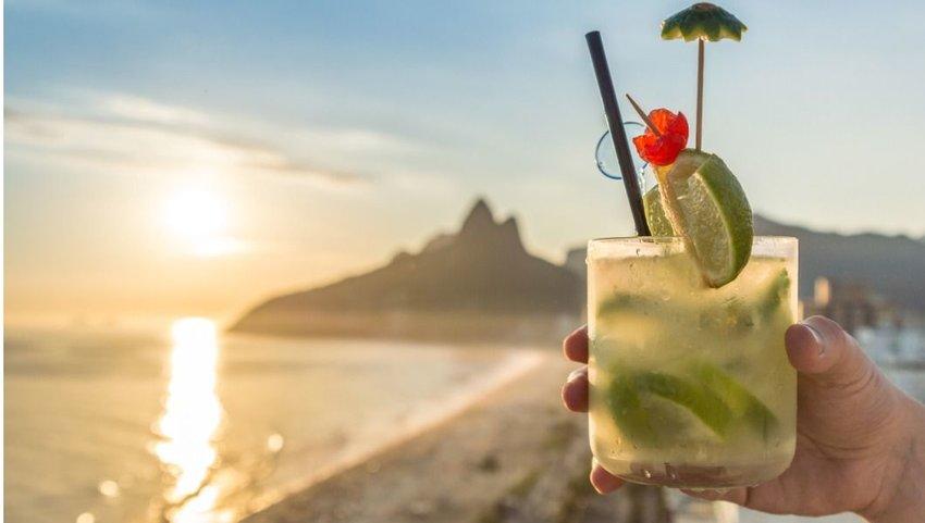 Person holding a Caipirinha cocktail on the beach of Rio de Janeiro, Brazil