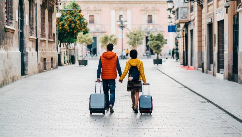 Traveling couple walking through street with luggage