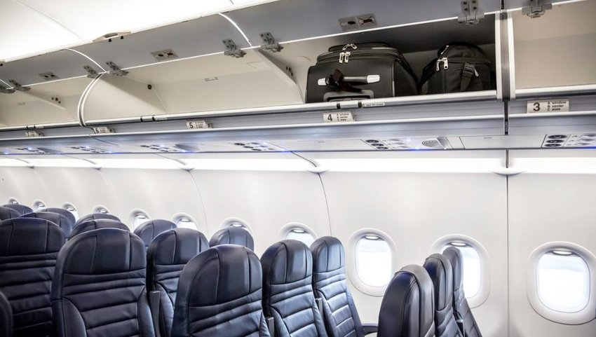 Side view of empty airplane interior with bags in the overhead luggage compartments