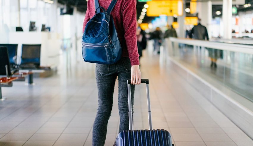 woman walking through airport with luggage
