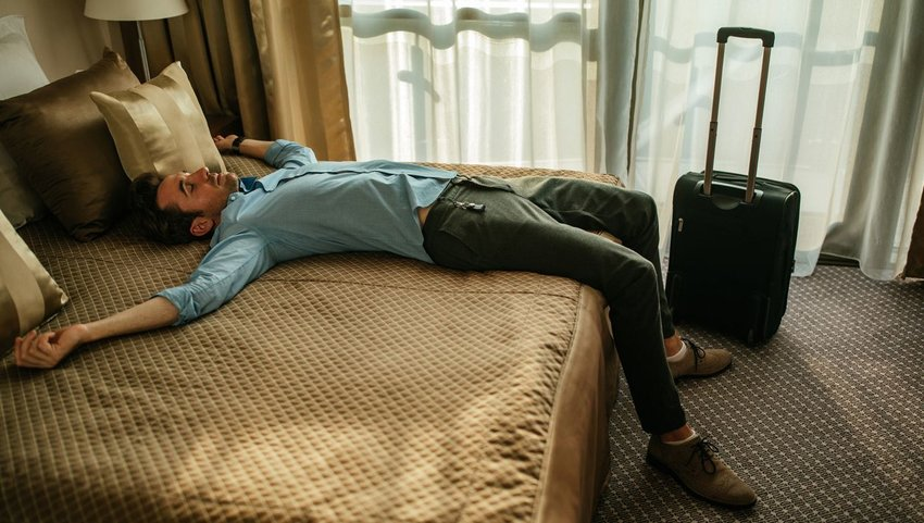 Man asleep on a hotel bed in daytime clothes and shoes