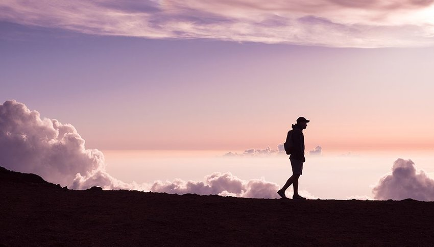 Man walking on a mountain ridge at sunrise with clouds in the background