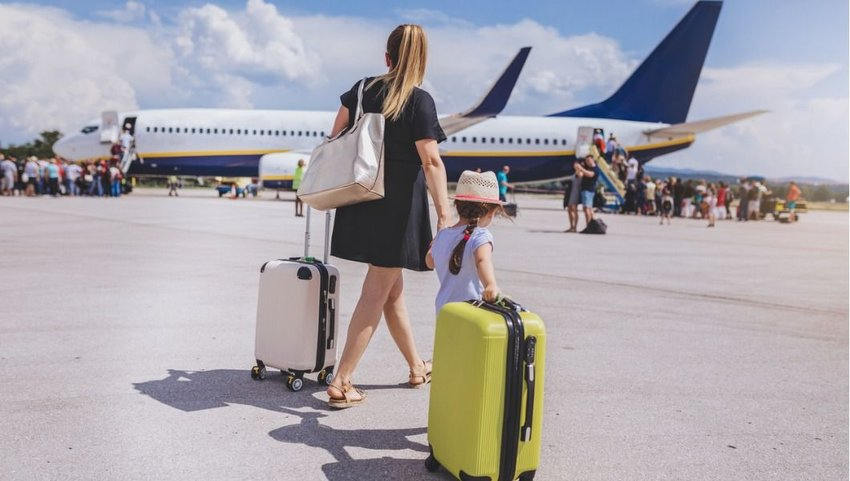 Mother and daughter boarding plane with large carry-on luggage