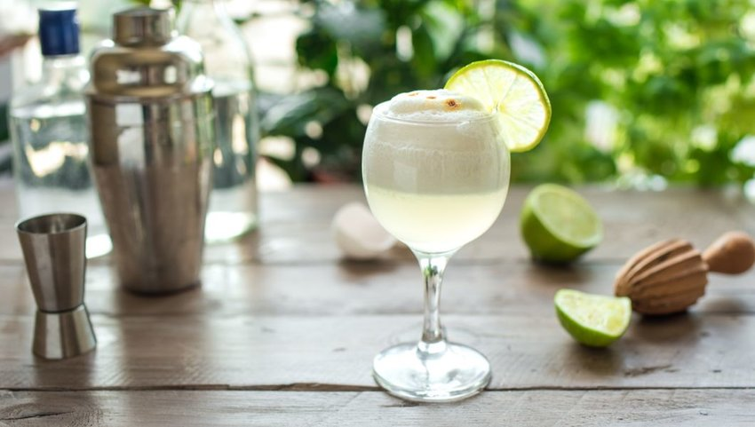 Front view of Pisco Sour cocktail on table with limes and shaker