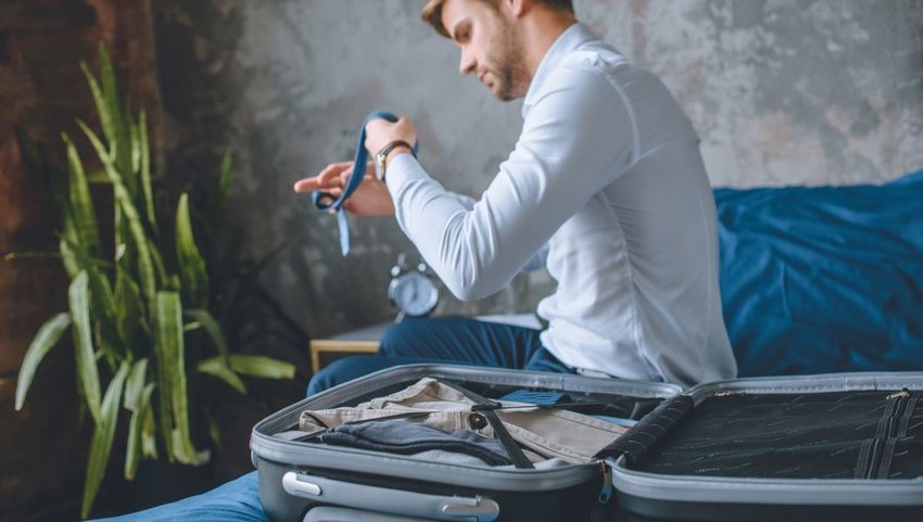 Businessman carefully packing suitcase in hotel room