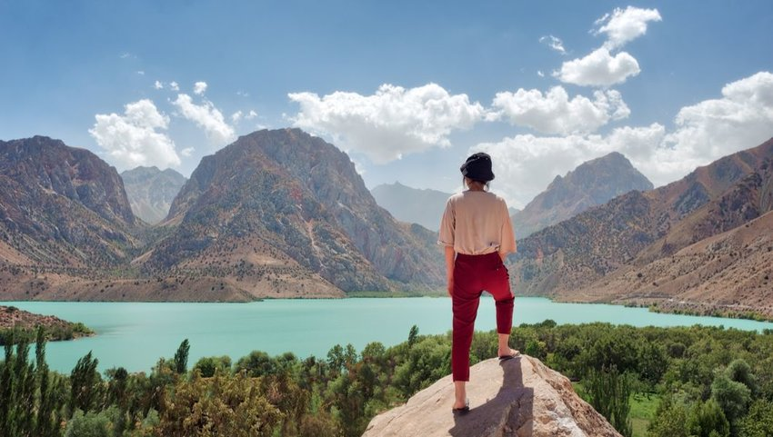 Woman overlooking Iskanderkul in the Fann Mountains, Tajikistan