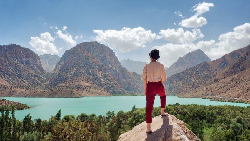 Woman overlooking Iskanderkul in the Fann Mountains, Tajikistan