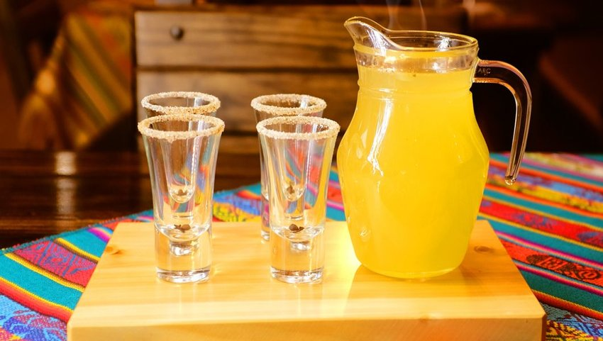 A pitcher of Canelazo, a hot cider drink, on a table with glasses