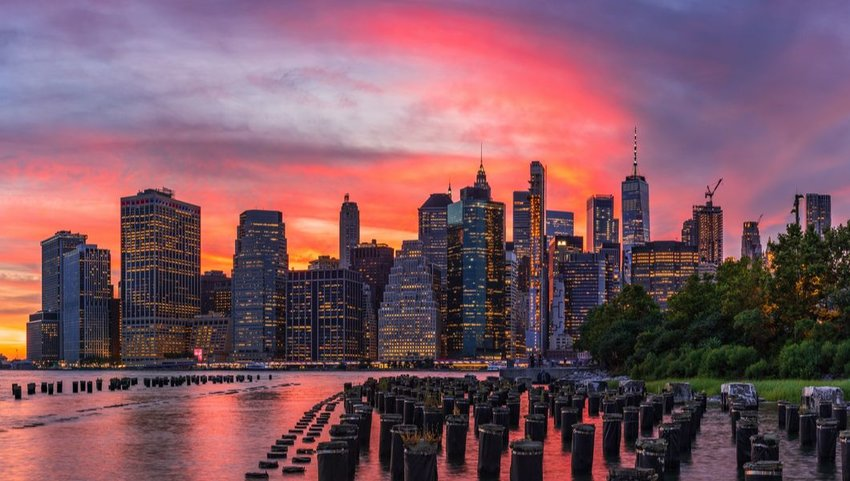 Red sky sunset over New York City skyline from Brooklyn Bridge Park