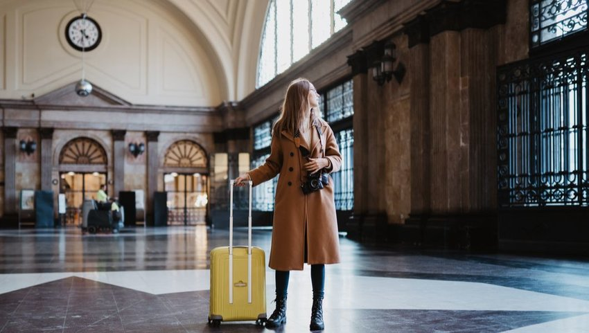 Woman in trench coat and boots with bright yellow suitcase