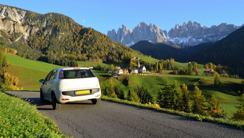 White car in autumn driving through the Funes Valley in the Dolomites, South Tyrol, Italy
