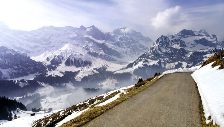 Narrow road in the Swiss Alps overlooking snow covered mountains