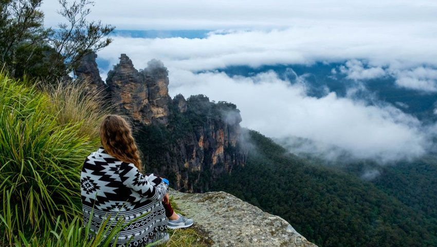 Woman relaxing on cliff overlooking the Three Sisters Rocks, Katoomba, New South Wales, Australia