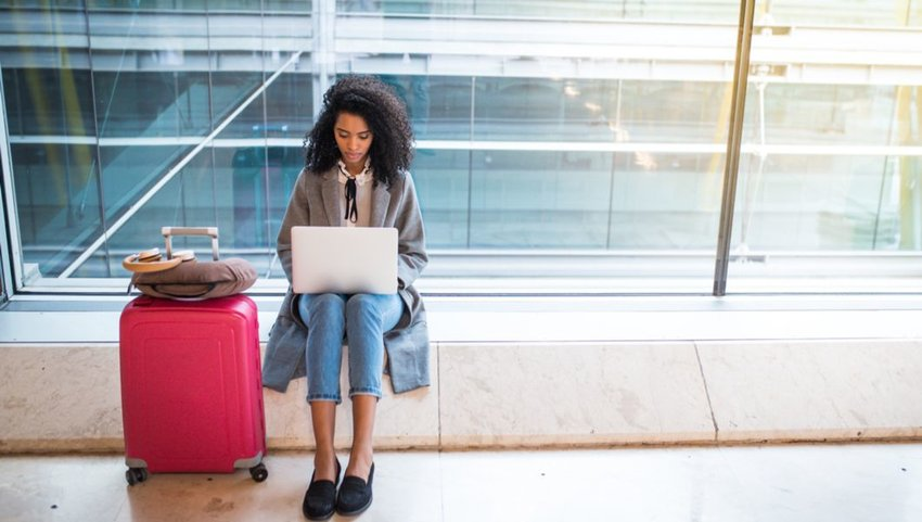 Woman with large suitcase working on laptop in airport terminal