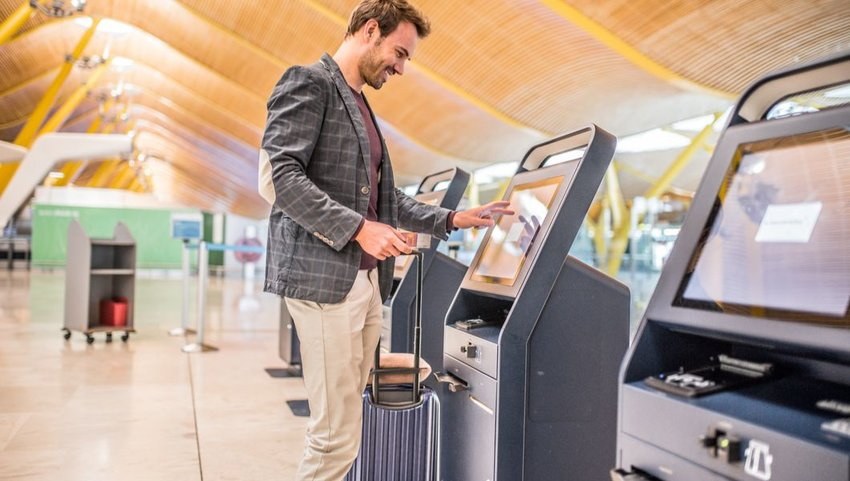 Male traveler using self check-in machine at the Madrid–Barajas Airport