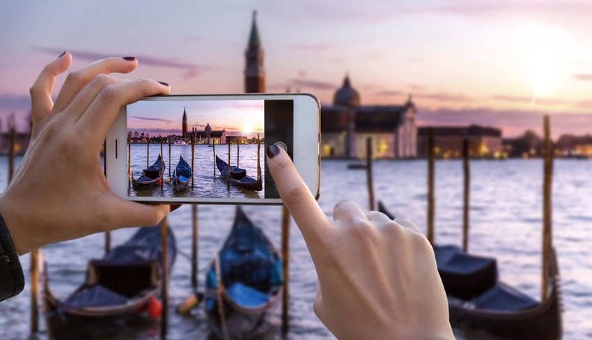 tourist hands taking photo of Venice canal