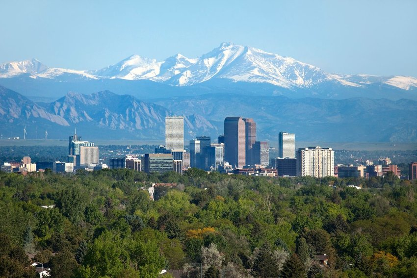View of Denver, Colorado surrounded by trees with mountains in background
