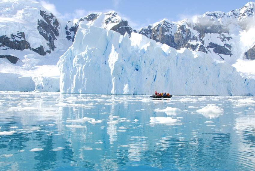 People in a boat next to an iceberg