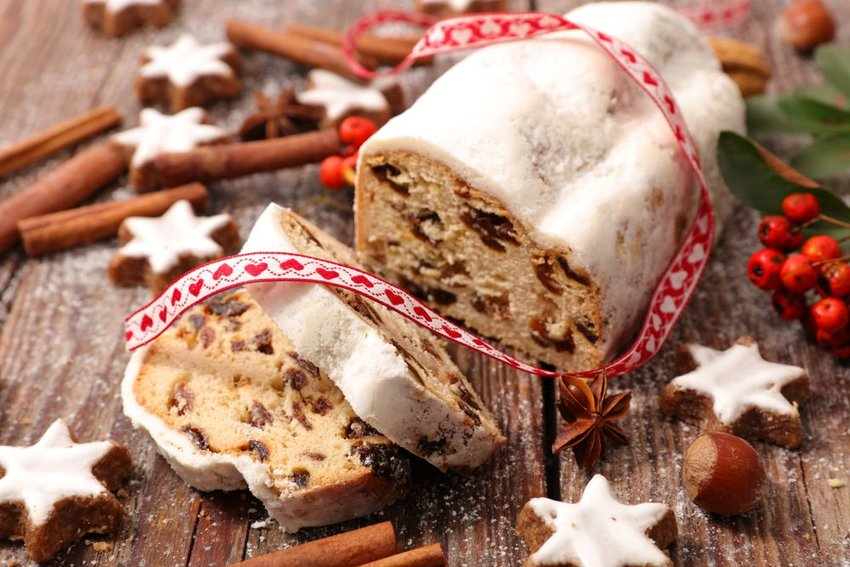 Loaf of Stollen on wood table, surrounded by Christmas cookies