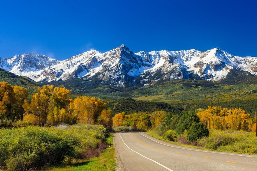 Road to rocky mountains covered in snow in fall