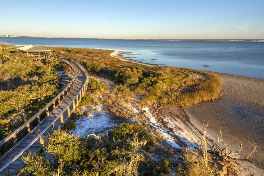 A boardwalk curves over the vegetation on the dunes in Big Lagoon State Park in Florida