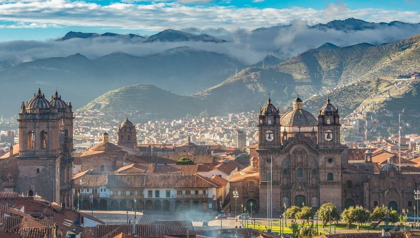 Morning sun rising at Plaza de armas with Adean Moutain in background, Cusco, Peru