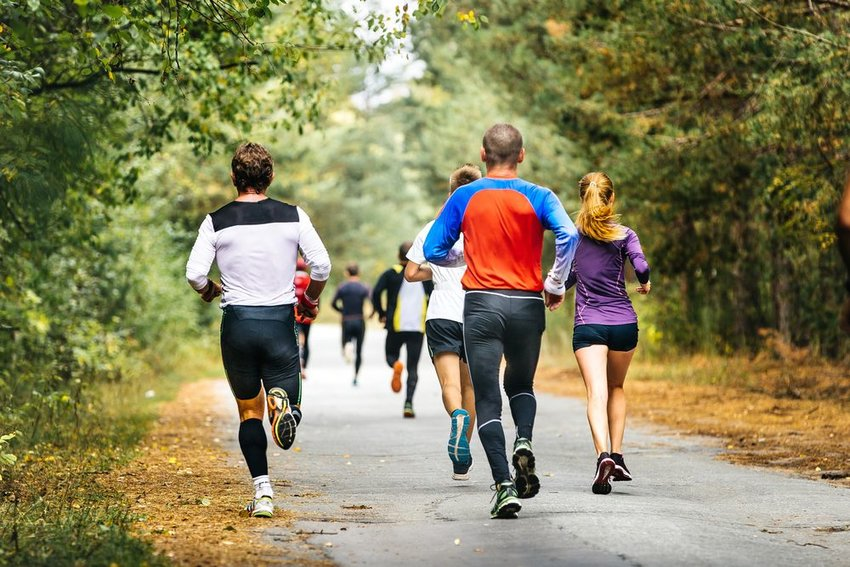 Group of people jogging down a road on a fall day