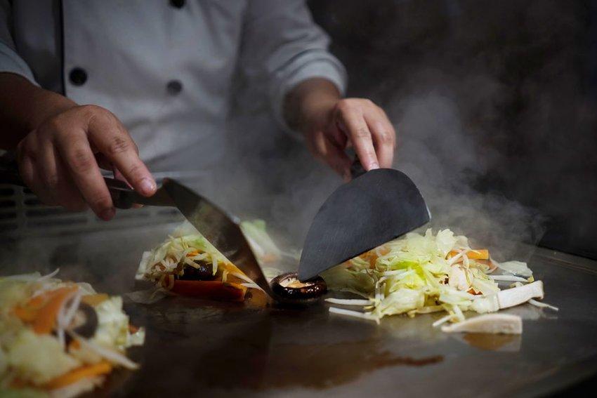 Japanese Teppanyaki chef cooking in an open restaurant kitchen