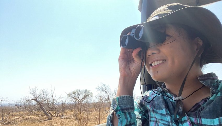 The author on a wildlife expedition, looking through binoculars