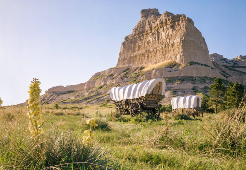 Covered wagons in front of rocky bluff at Scotts Bluff National Monument, Oregon Trail in Nebraska