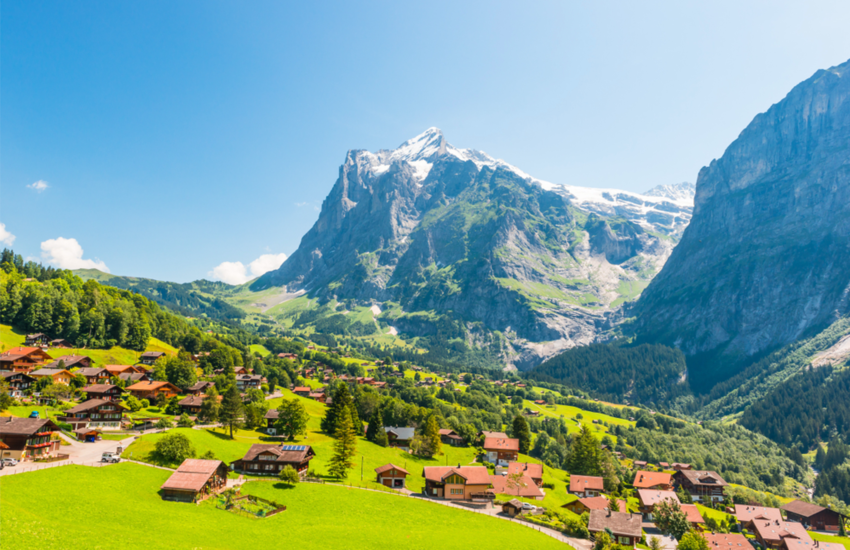 Town of Grindelwald on green landscape with huge mountain in background