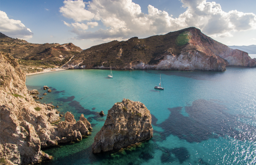 Two boats in clear water in bay of Milos island