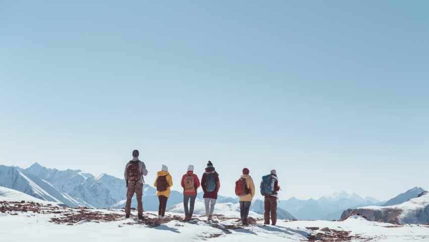 Group of backpackers standing at the top of a snowy mountain peak