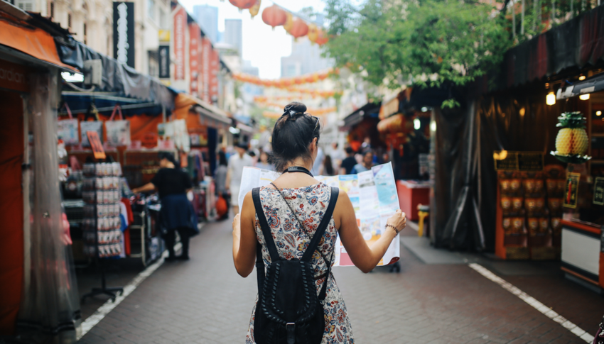 Woman looking at map while standing in center of street