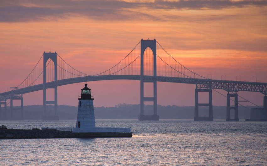 Goat Island Lighthouse with Newport Bridge in background at sunset