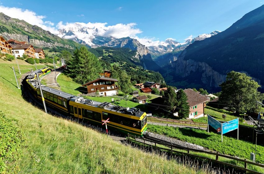 View of train traveling through the town of Wengen