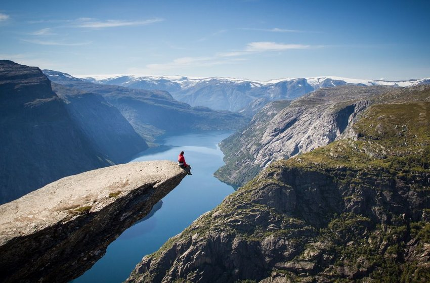 Person sitting on edge of Trolltunga cliff