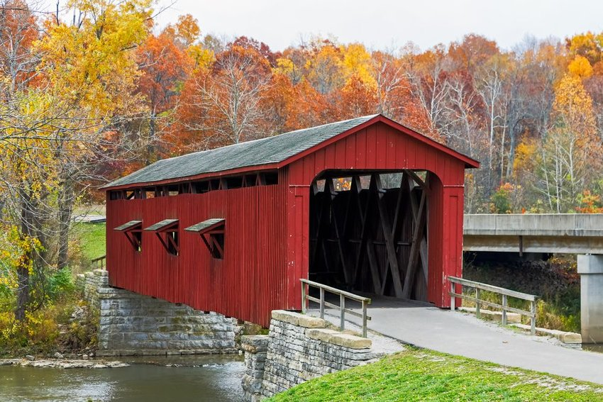 The historic red Cataract Covered Bridge crosses Indiana's Mill Creek with fall trees